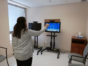 Woman trying out an activity with the right arm on the Jintronix Wave